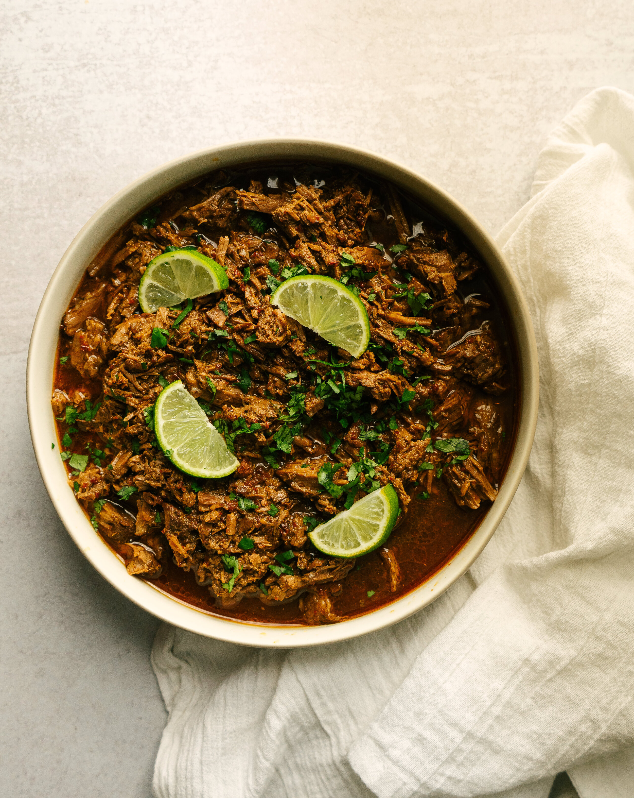 above view of beef barbacoa in a bowl with cilantro and lime slices on top