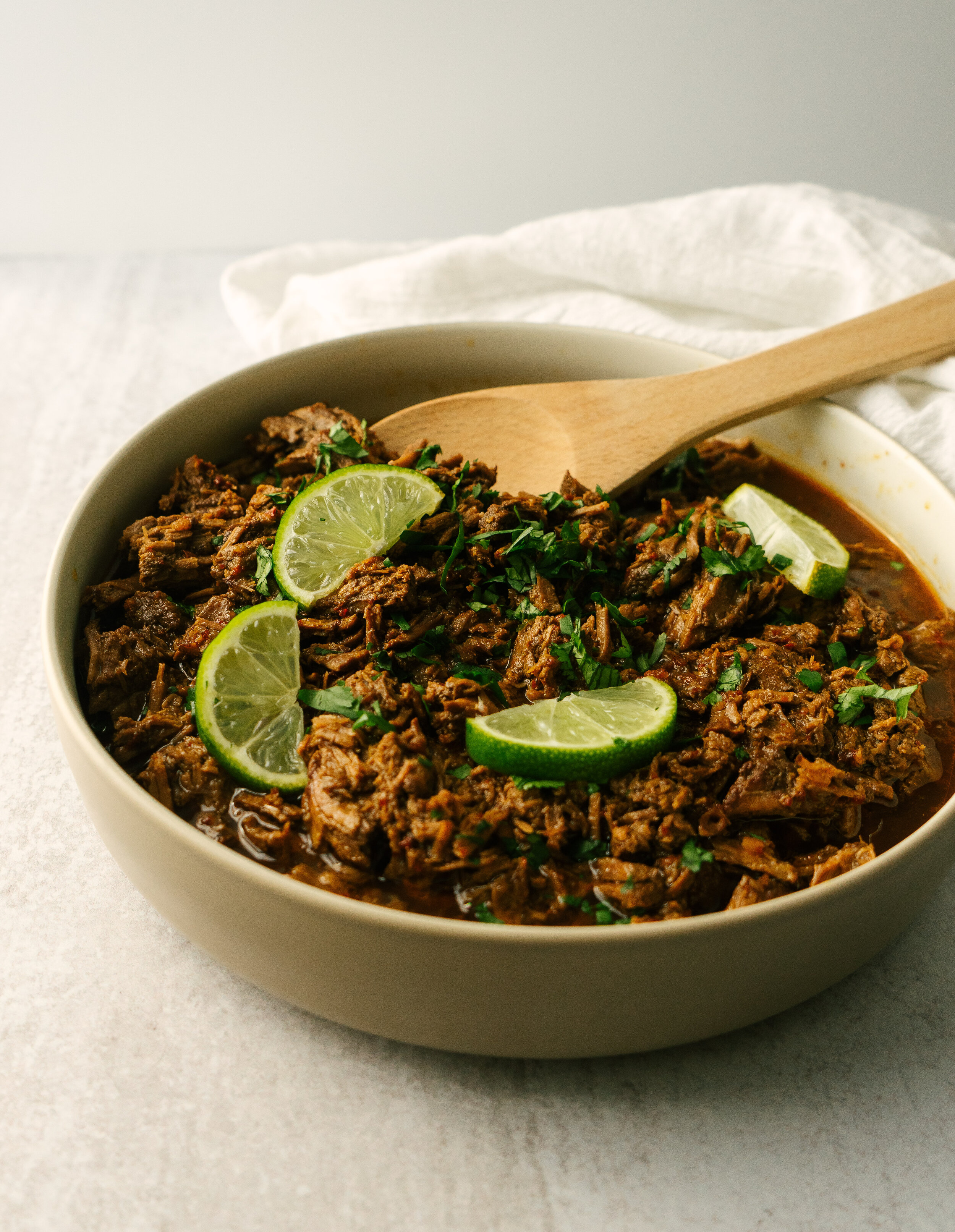 three quarter view of a bowl of instant pot barbacoa with a spoon in it