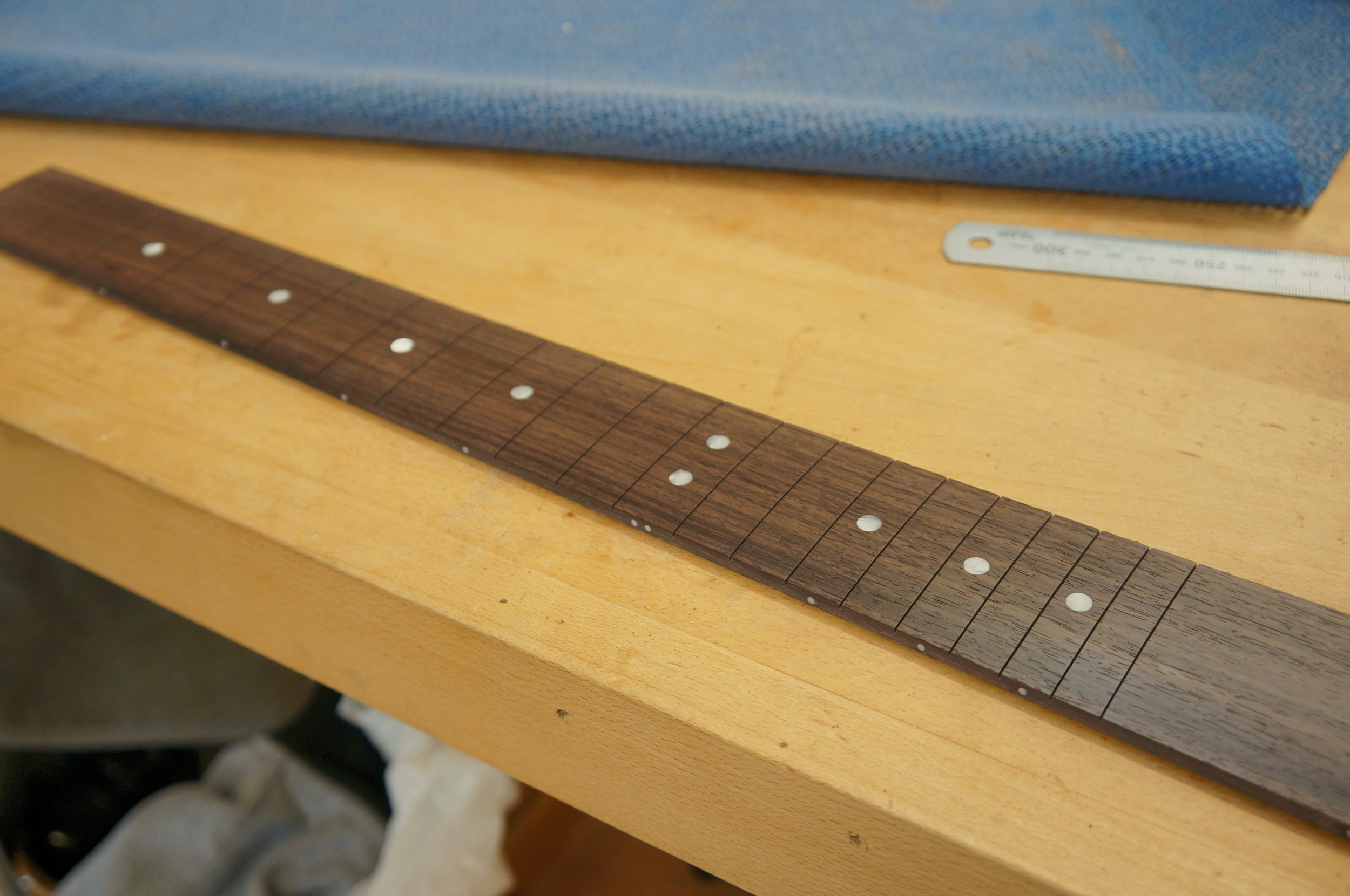 rosewood fingerboard position dots glued and sanded back, fretslots all cut.JPG