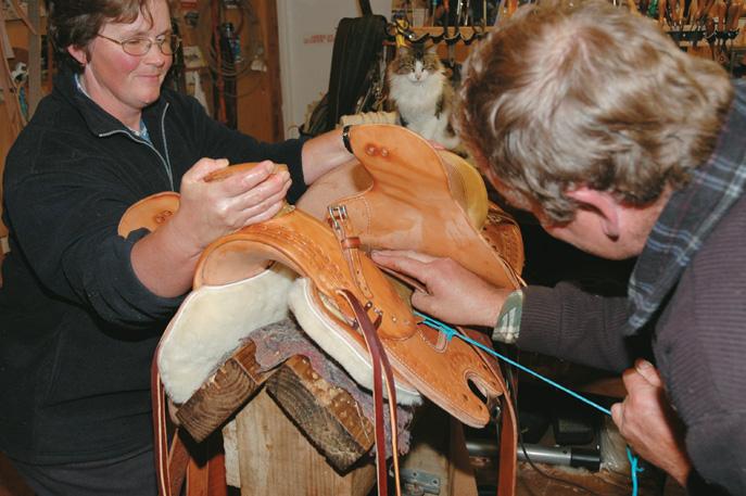 Jane helps as Graeme pulls leathers through beneath the skirt