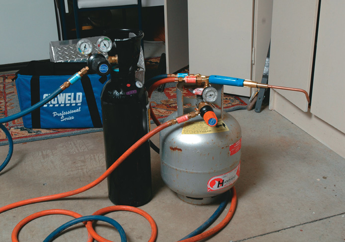 Black oxygen and silver LPG tank. Nte orange hose for LPG