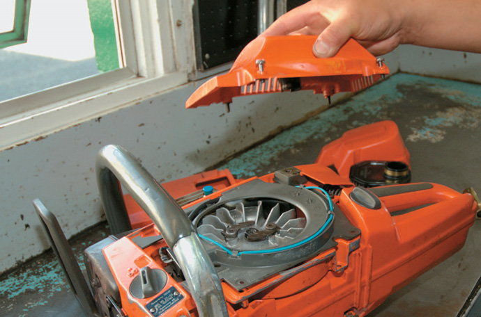 Removing the side cover to expose the flywheel and coil