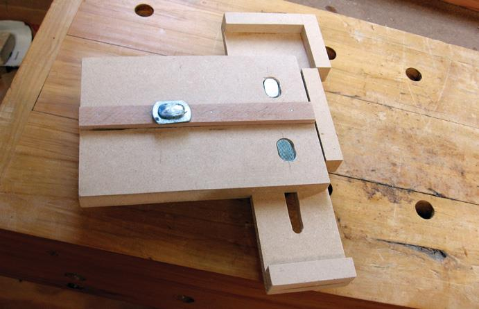 Two T bolt heads in slots hold the sliding mechanism in place. Small feet on either end act as stops and support the wood being cut.