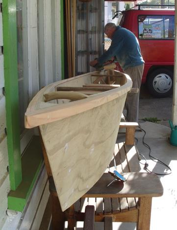 Strips of wood glued make the coaming. Short spreader is near front to allow room for paddles and outrigger to slip into the canoe for carrying.