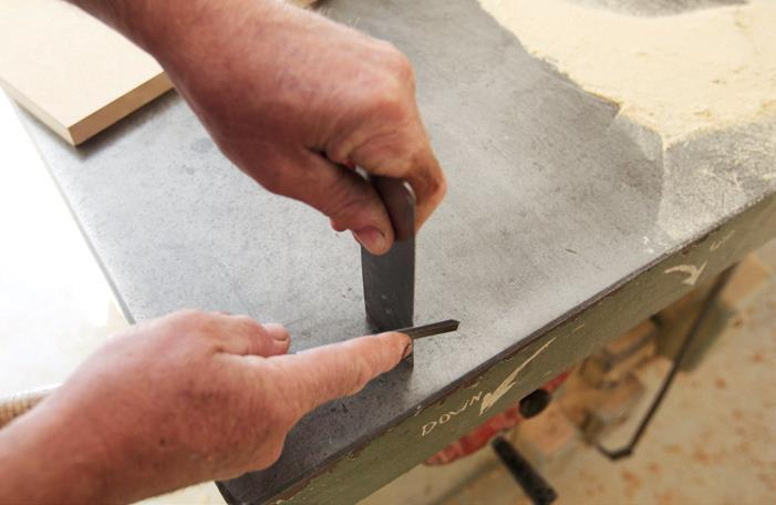 Neil sharpening the scraper with an old chisel.