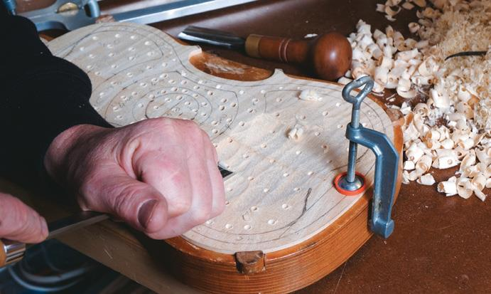 Working across maple back, held by solid jig.