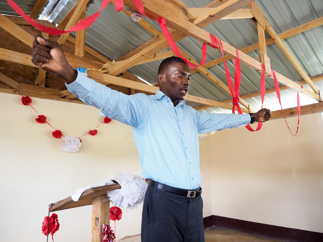 Pastor Fednel praying at Cross to Light Church, Caanan