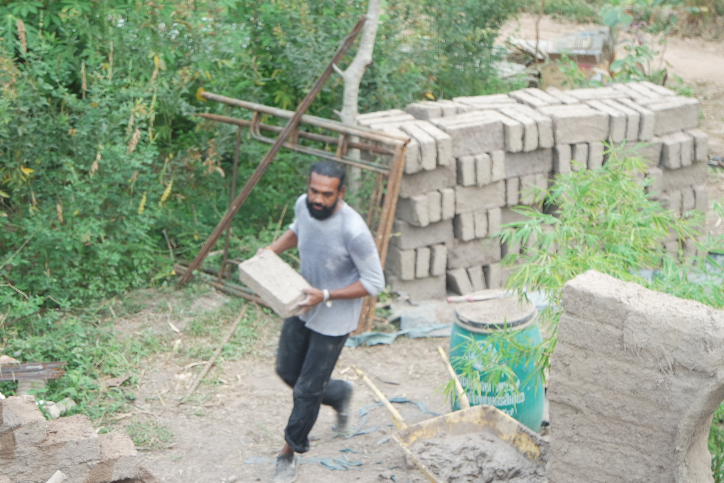 Taking turns and supporting people laying bricks with material is an important part of the work.