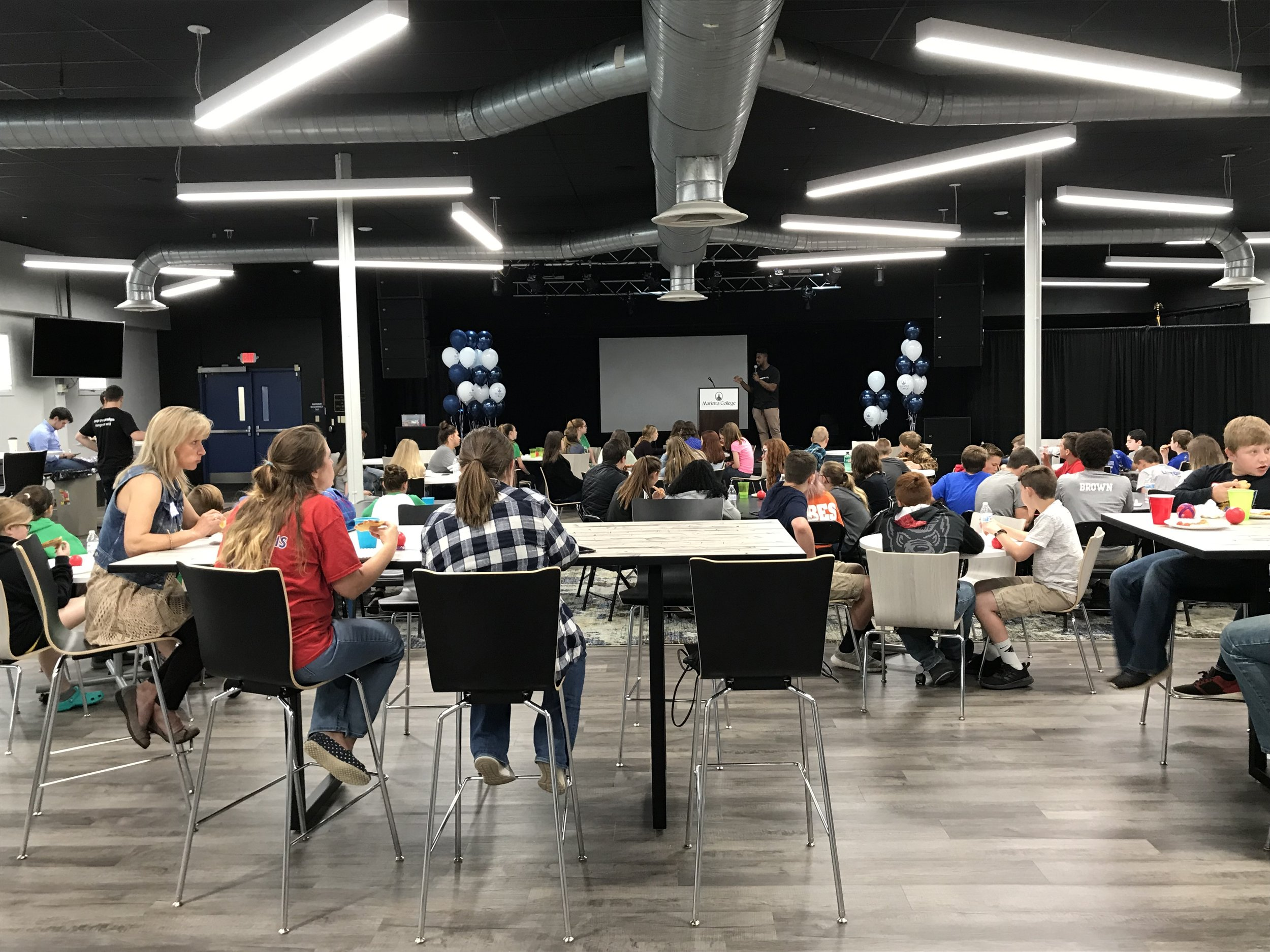 Over 100 students enjoy a presentation during their lunch.