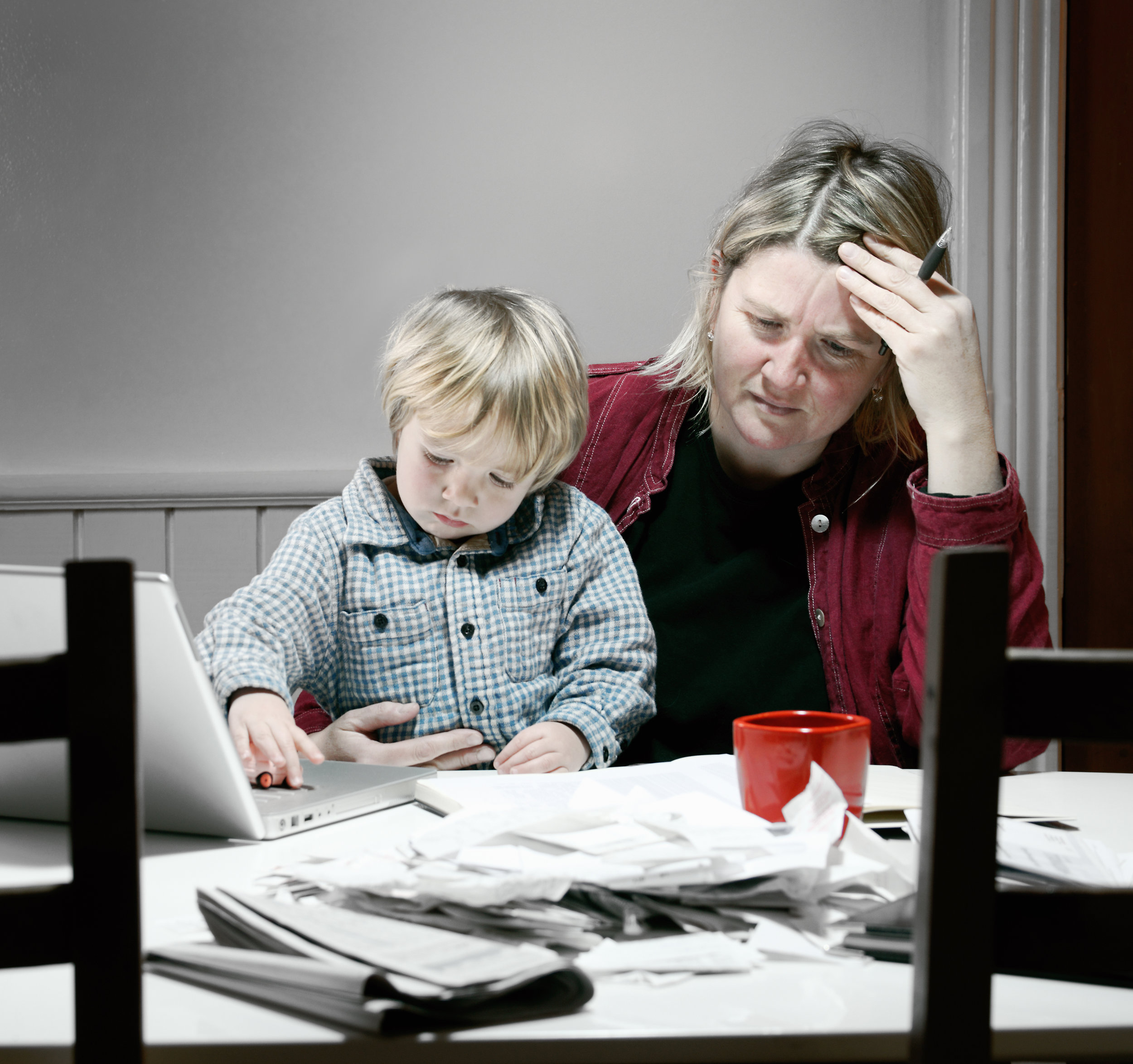 stock-photo-15256471-stressed-and-tired-mother-working-on-financial-issues_tint.jpg