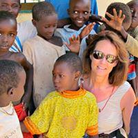 Little girl in yellow near Susanne was the first surgery recipient in 2003