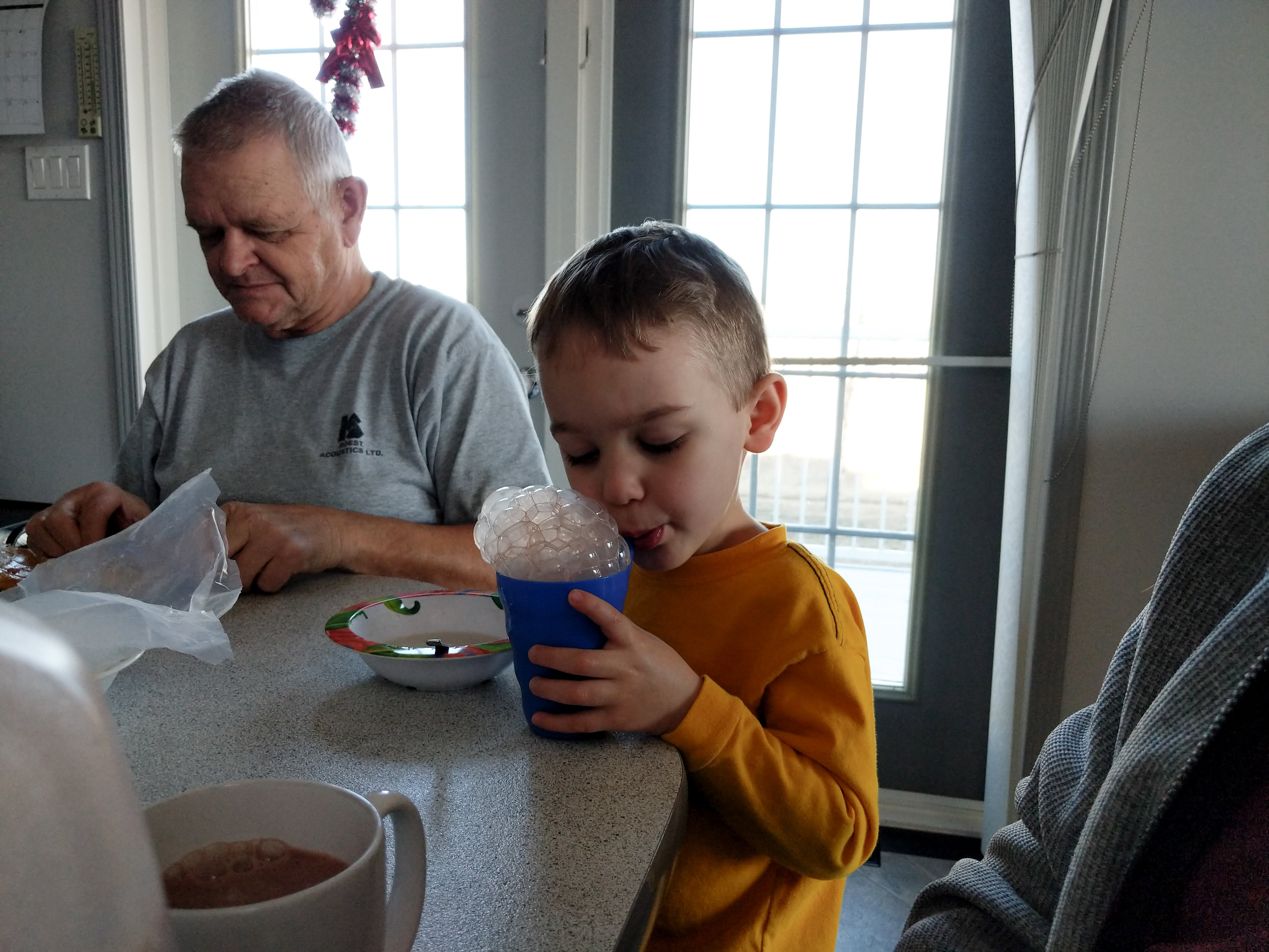 Grandpa the adult in this picture has shown the grandkids the best things. Like making bubbles with your chocolate milk and sugar on buns.