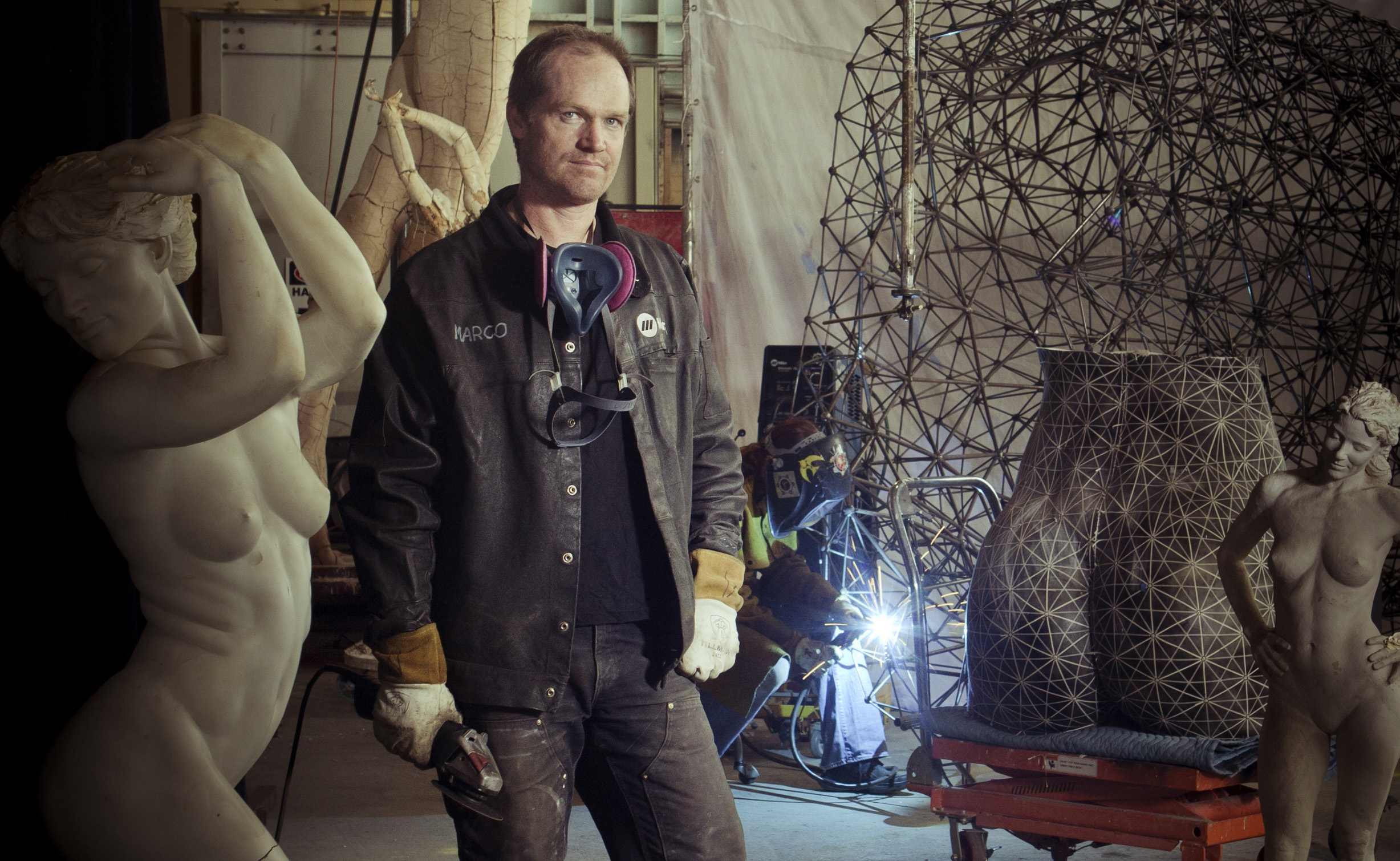 "Marco Cochrane in his Treasure Island Studio on San Francisco Bay working on his latest 50 foot tall sculpture ""Truth and Beauty"" Photographed by Thomas Kuoh."