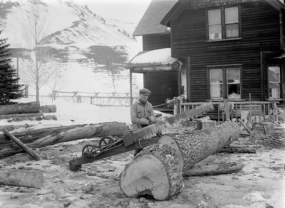 Working hard to get enough wood cut for a long Jackson winter. The house in this photo (now painted white) is still the ranch headquarters today.