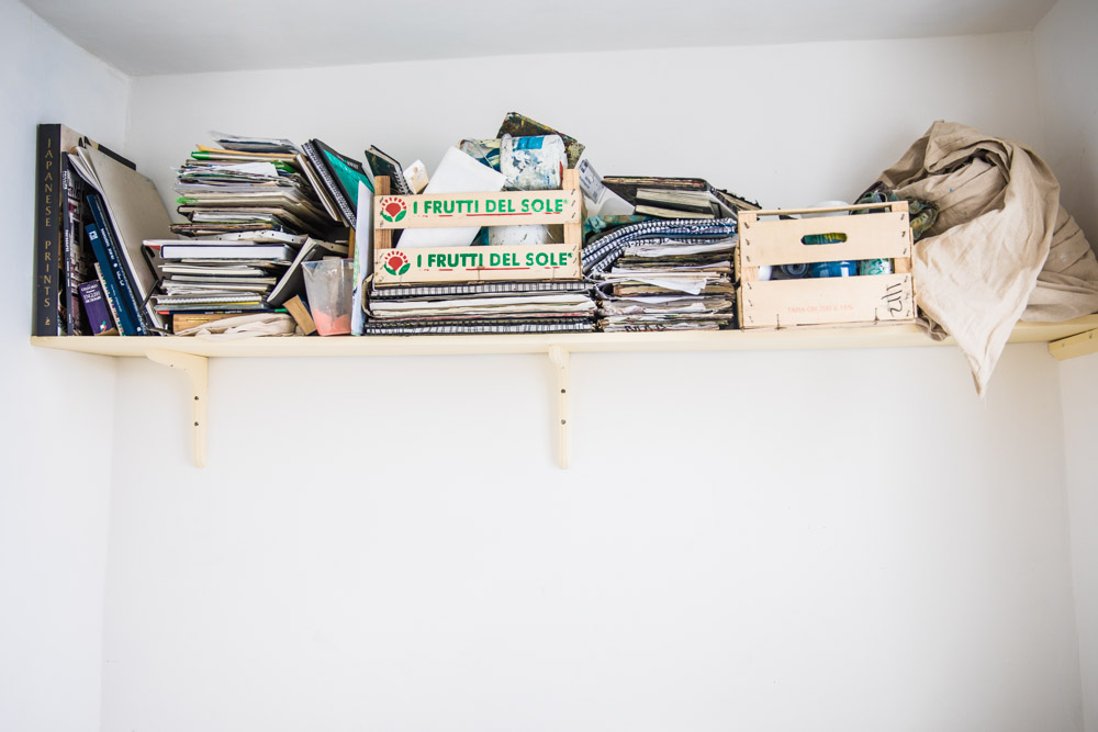 High cluttered shelf white walls