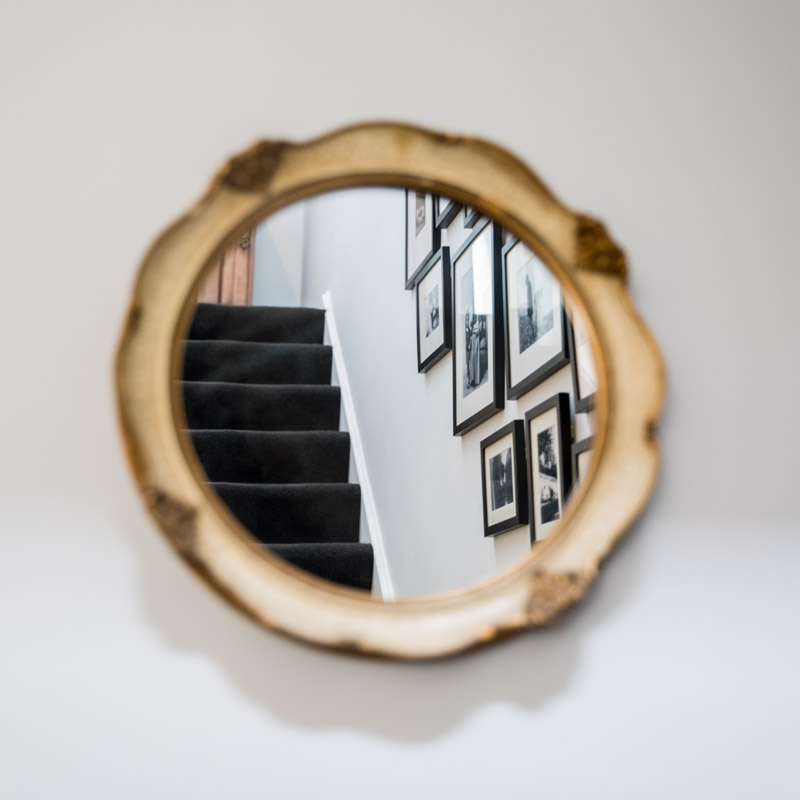 Round gold mirror reflecting gallery wall on the stairs