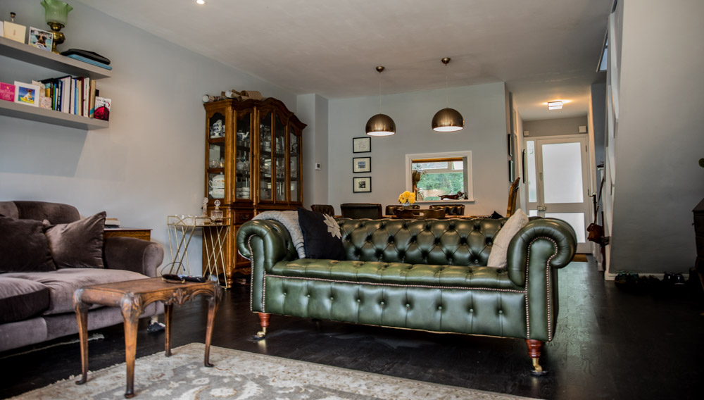 Green chesterfield lounge area with various antique furniture