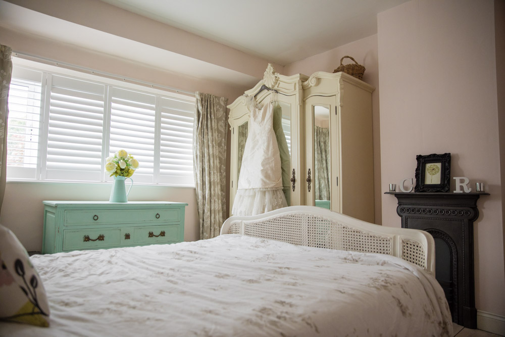 Light and airy bedroom with dark fireplace and wedding dressing