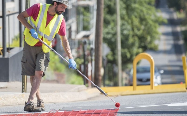 Safe streets advocate Michael Ward paints a decorative brick pattern at the intersection of Church and Center in Fayetteville. Photo by J.T. Wampler of the Northwest Arkansas Democrat-Gazette.
