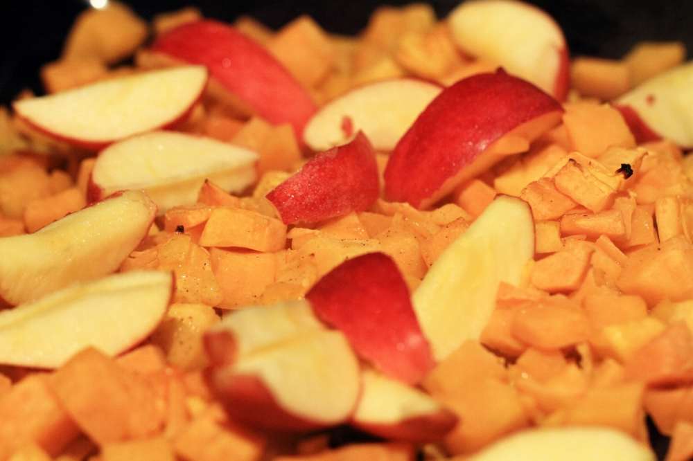 Apples and onions have been added in, preparing to return the pan to the oven.