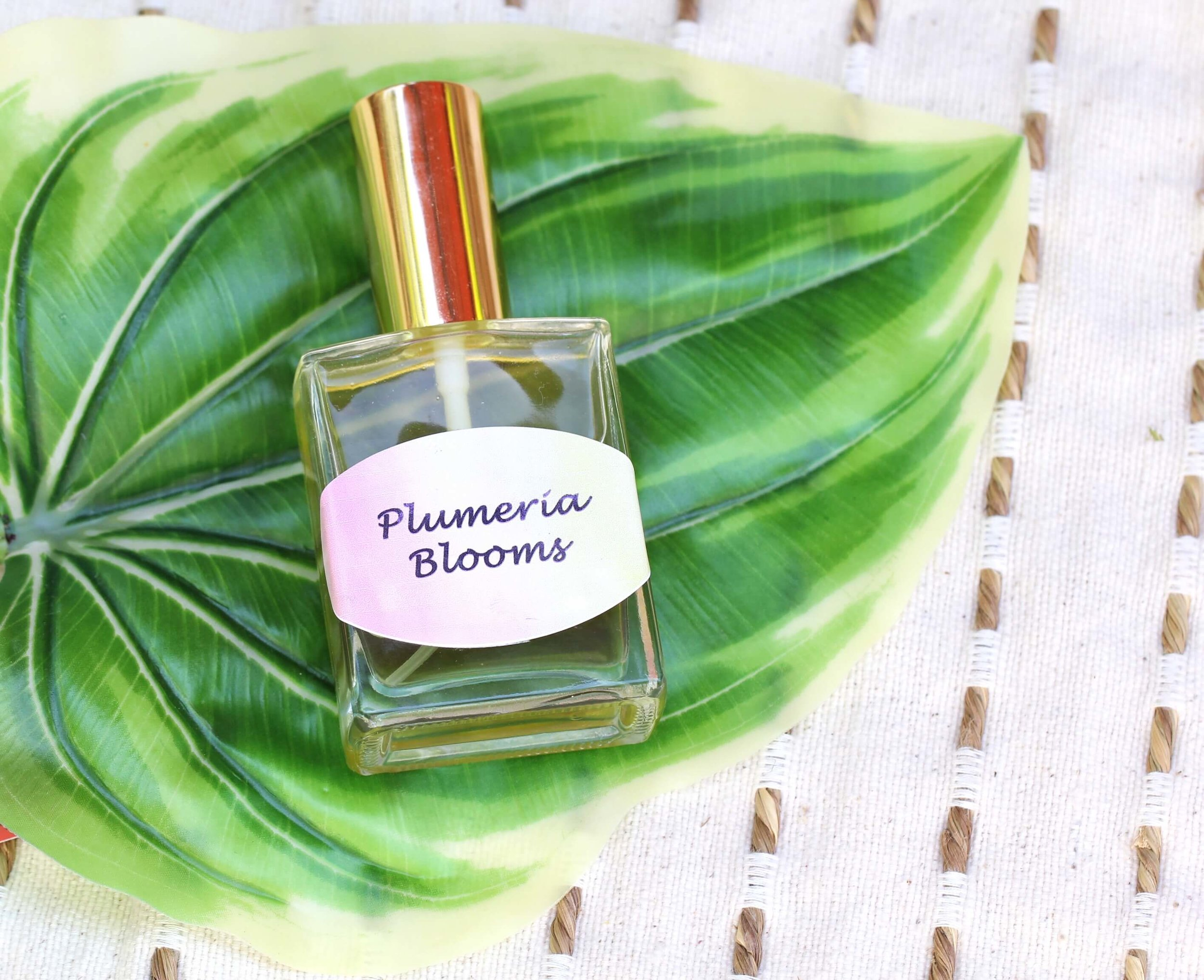 How to make DIY Perfume using fragrance oils and essential oils. The Plumeria scent provides a tropical oasis feeling for everyday! Plus free printable labels!