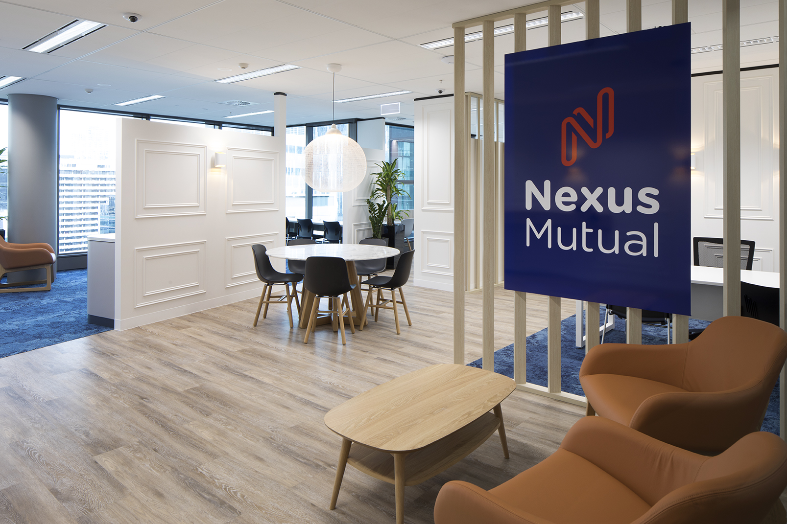 The Nexus Mutual Office fitout features wood panelling, lounge and breakout areas as well as a private members lounge.