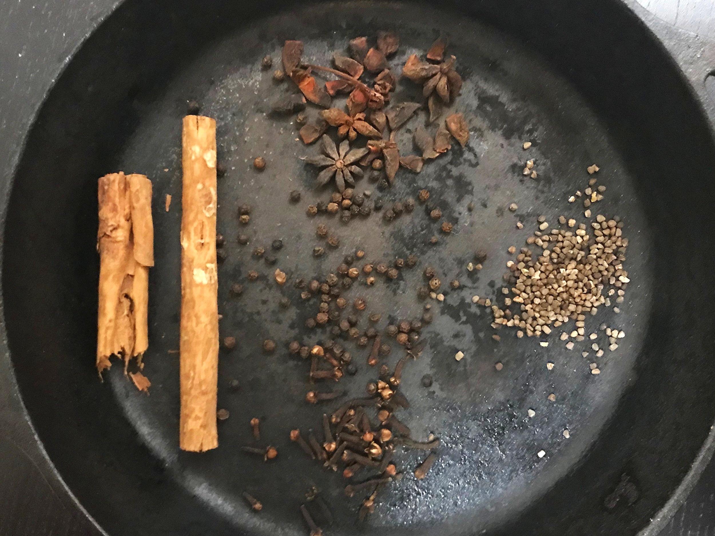 From left to right, clockwise: cinnamon sticks, star anise, cardamom, cloves. Center: peppercorn