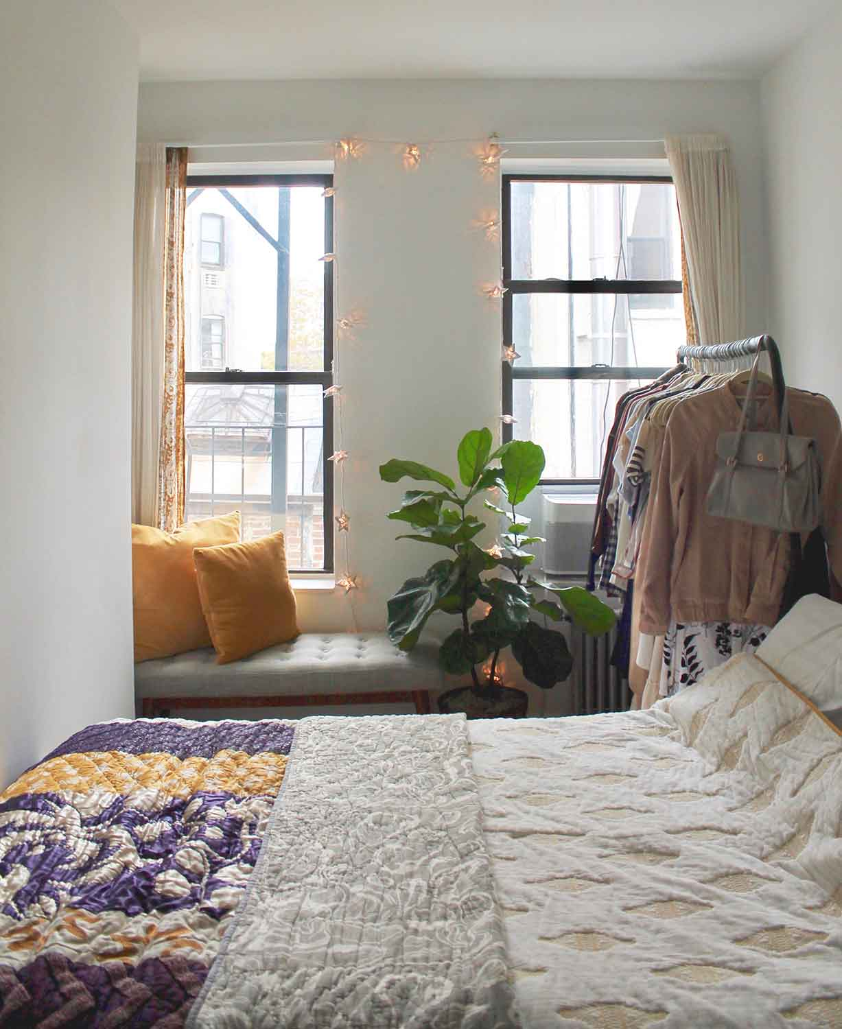 Bedding:  Anthropologie  // Window Seat:  West Elm  // Throw Pillows:  World Market  // Twinkle Lights:  World Market  // Curtains:  Urban Outfitters  // Clothing Rack:  IKEA  // House Plant:  Fiddle Leaf Fig Tree