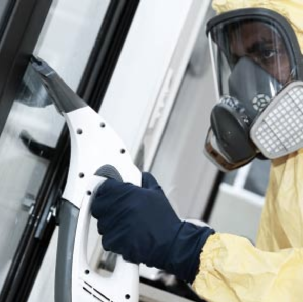 Man in yellow hazmat suit cleaning up after a biohazard incident