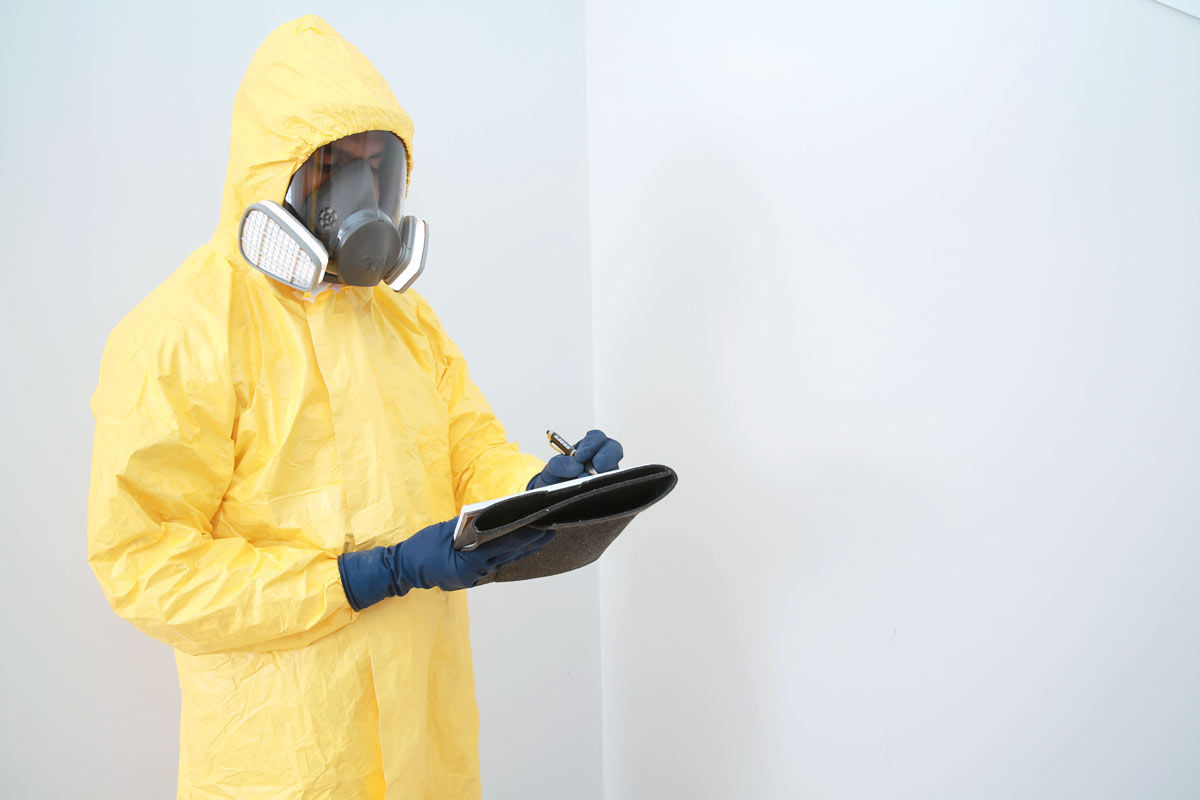 Man in hazmat suit checking home for asbestos