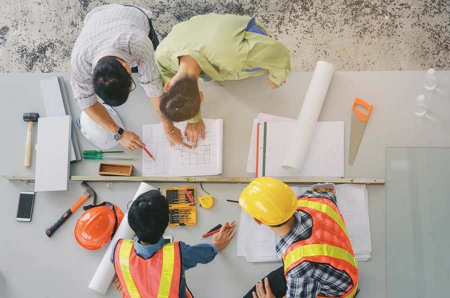 A group of employers looking at an asbestos management plan