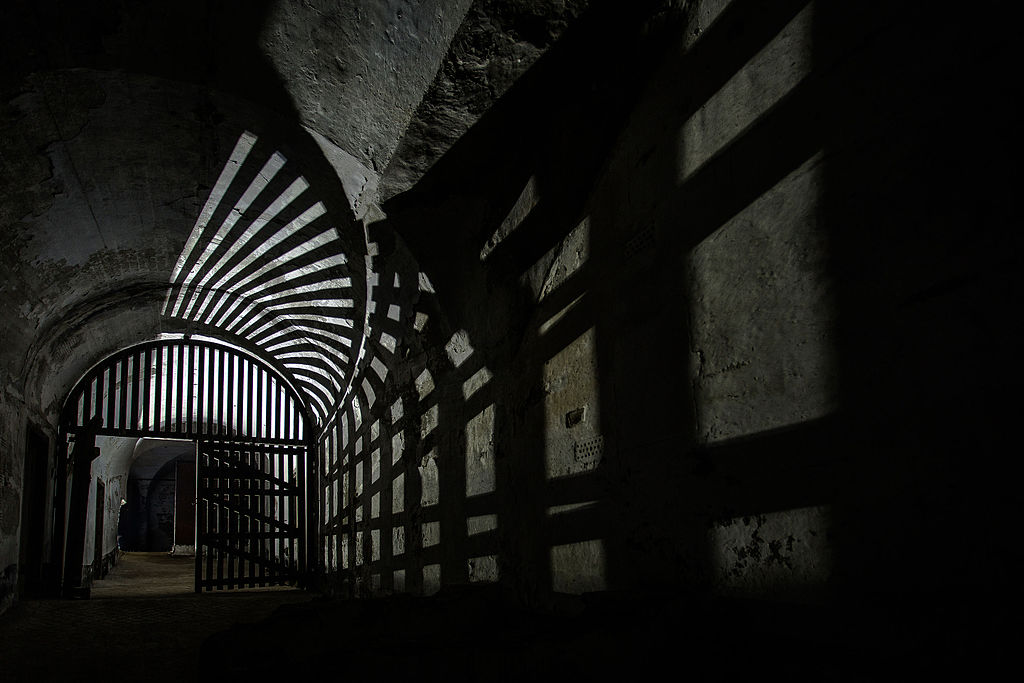 Something in a spooky abandoned asylum or prison or whatever. Photo by Twhelton [CC BY-SA 4.0 (https://creativecommons.org/licenses/by-sa/4.0)], from Wikimedia Commons