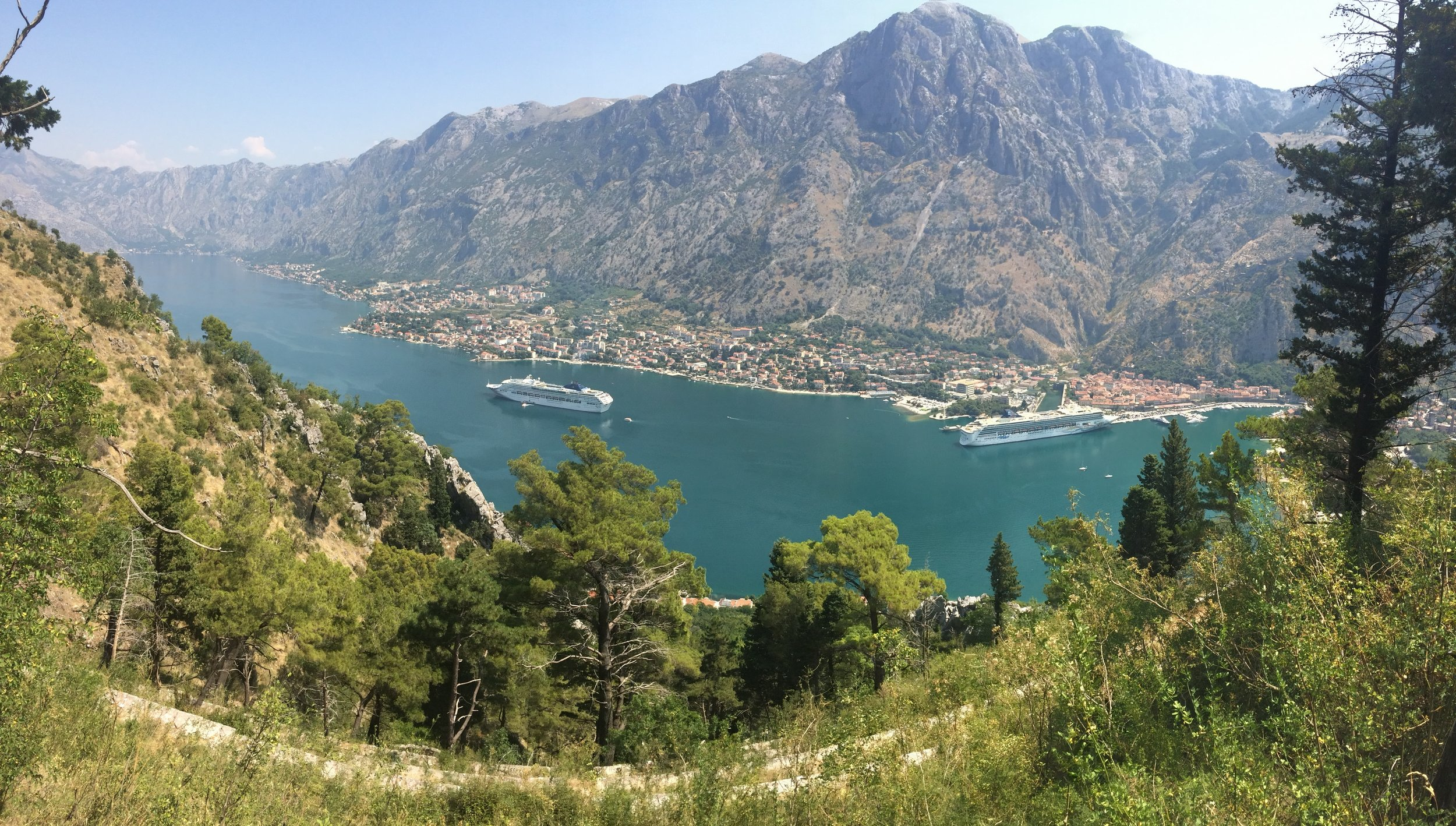 A cruise ship steams out of Kotor into the bay