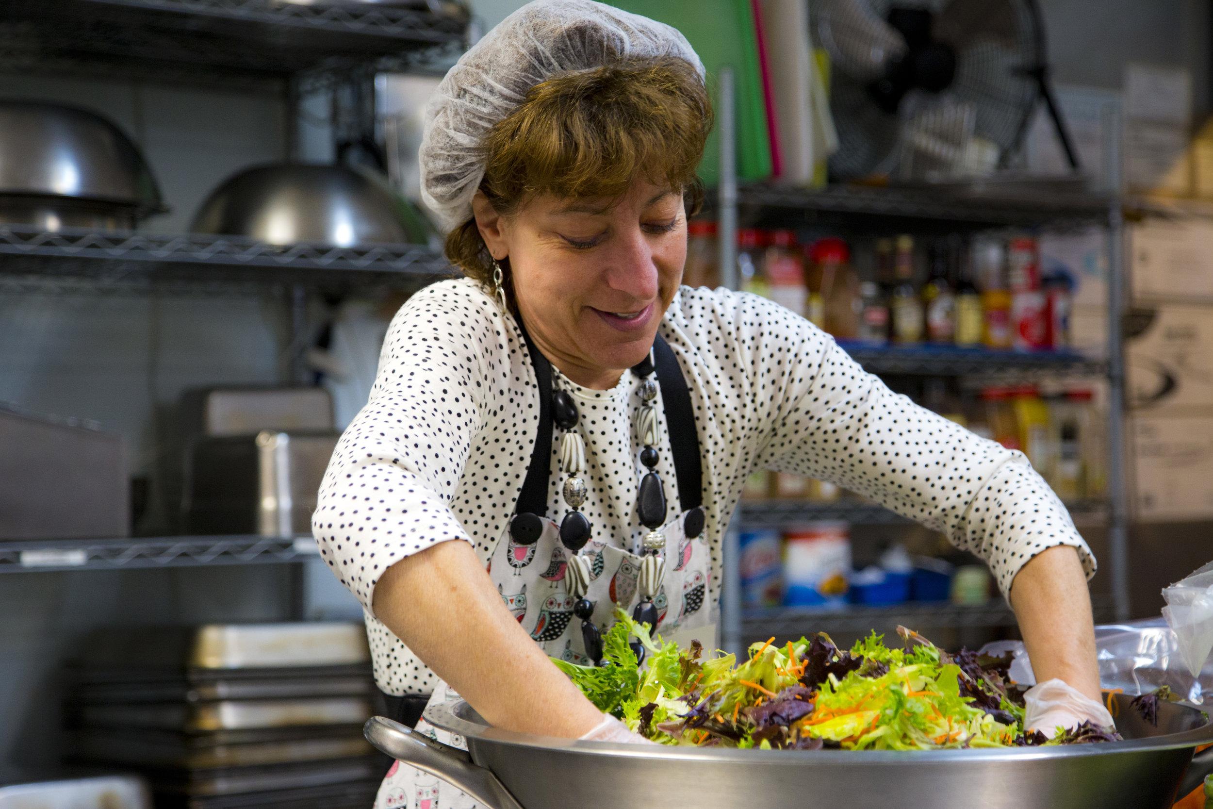 Volunteers help prepare healthy menus often including fresh produce..