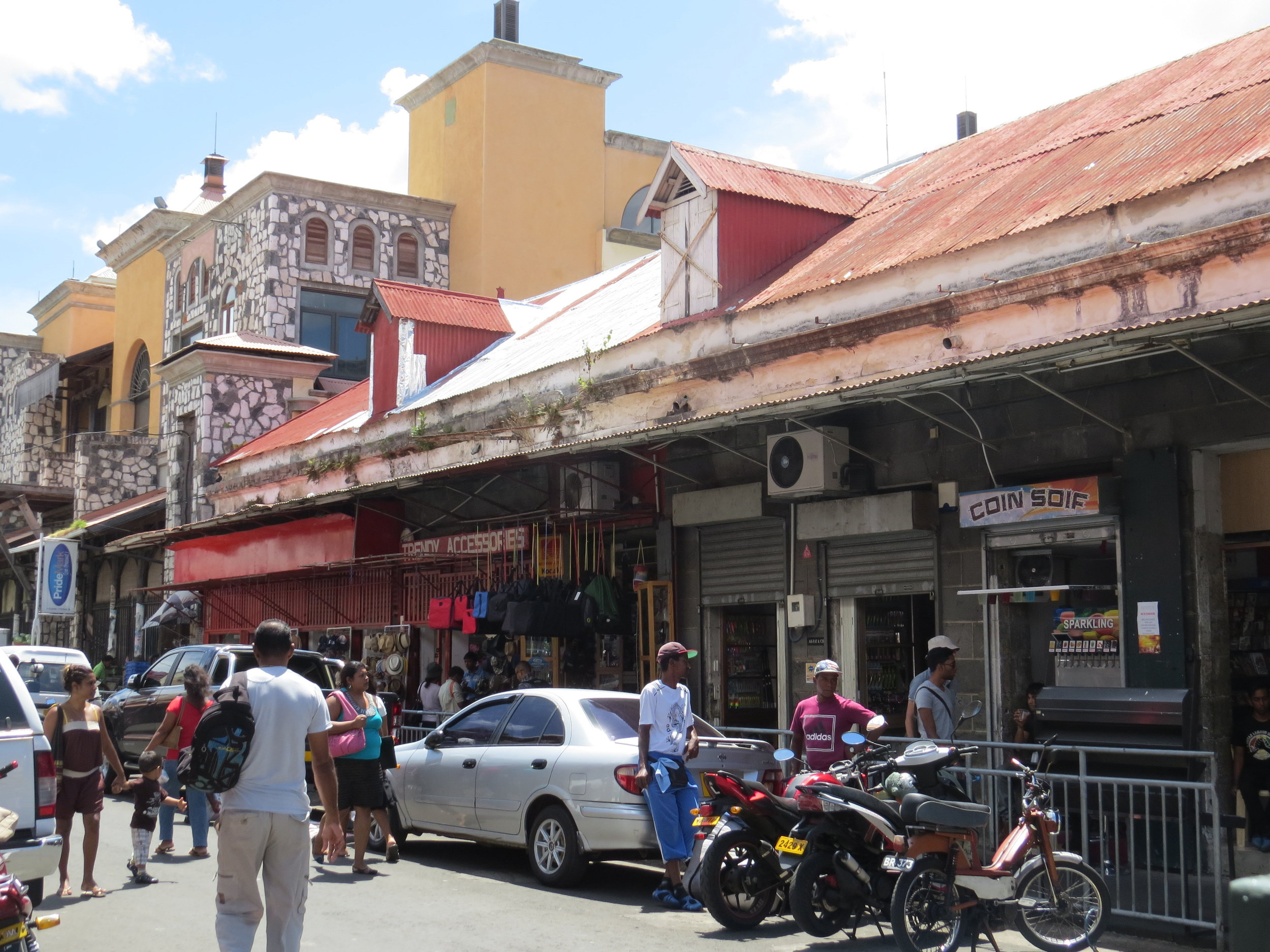 The streets are congested and pedestrian traffic overflows the narrow sidewalks which are crammed with vendor's wares.