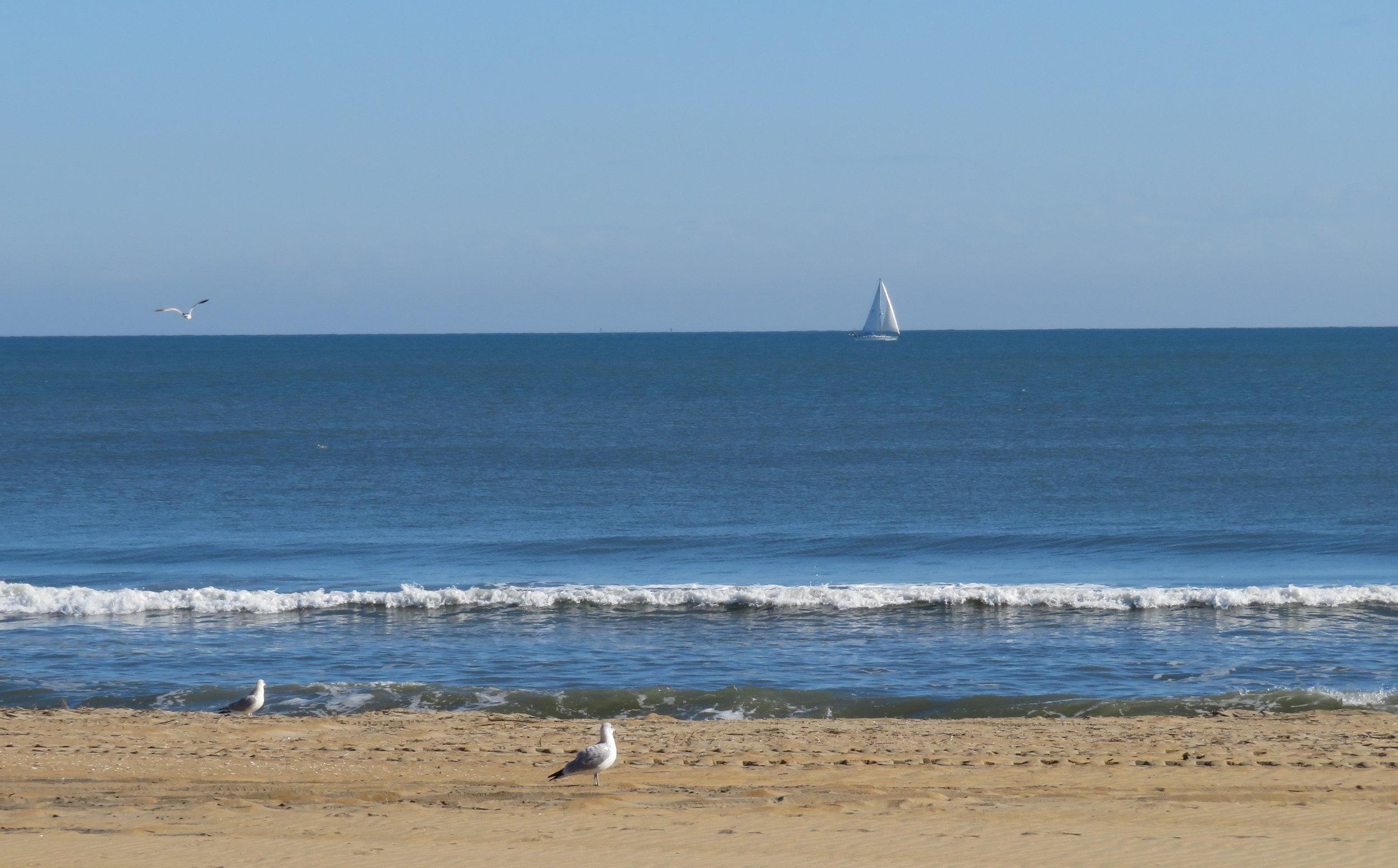 A lone sailboat skimmed along the horizon.