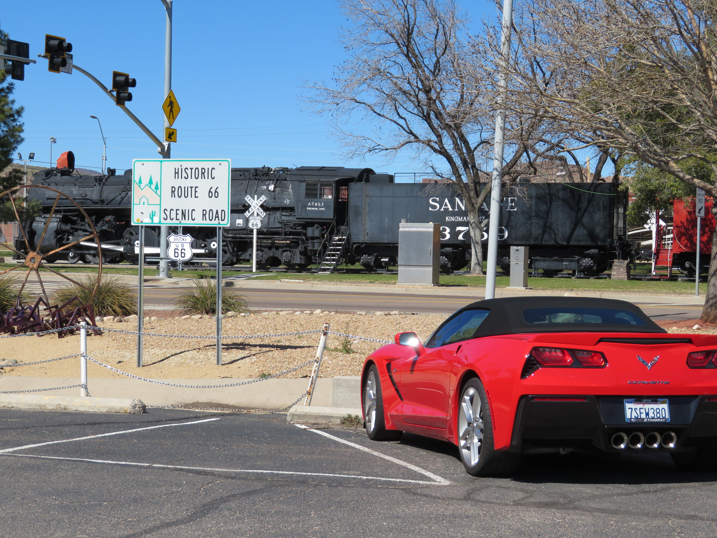 A shiny red Corvette was parked in front of the Route 66 sign at the Visitor Center. A Santa Fe RR engine is across the street at Locomotive Park.