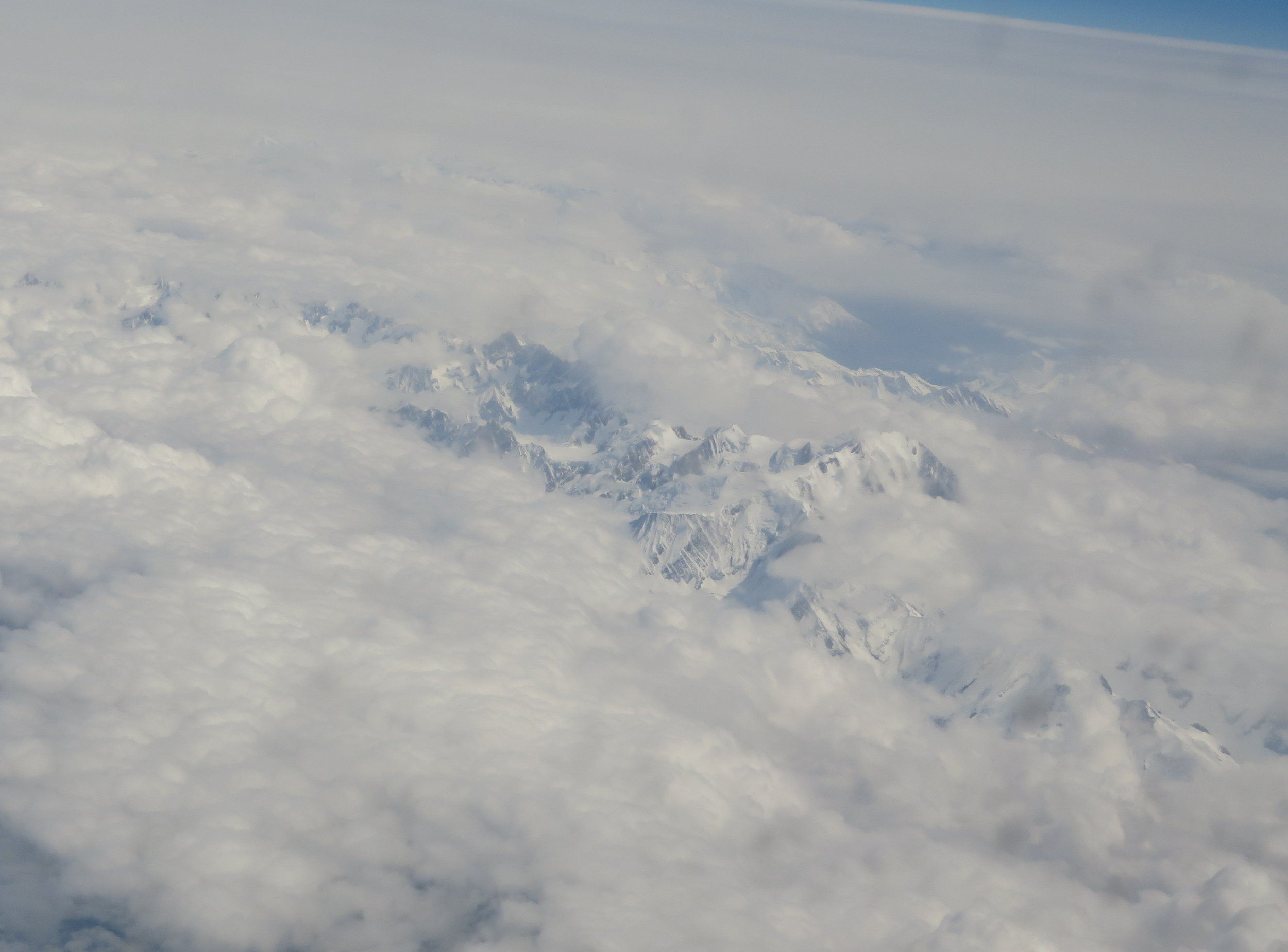 Snow-covered mountains peeked out of the clouds.