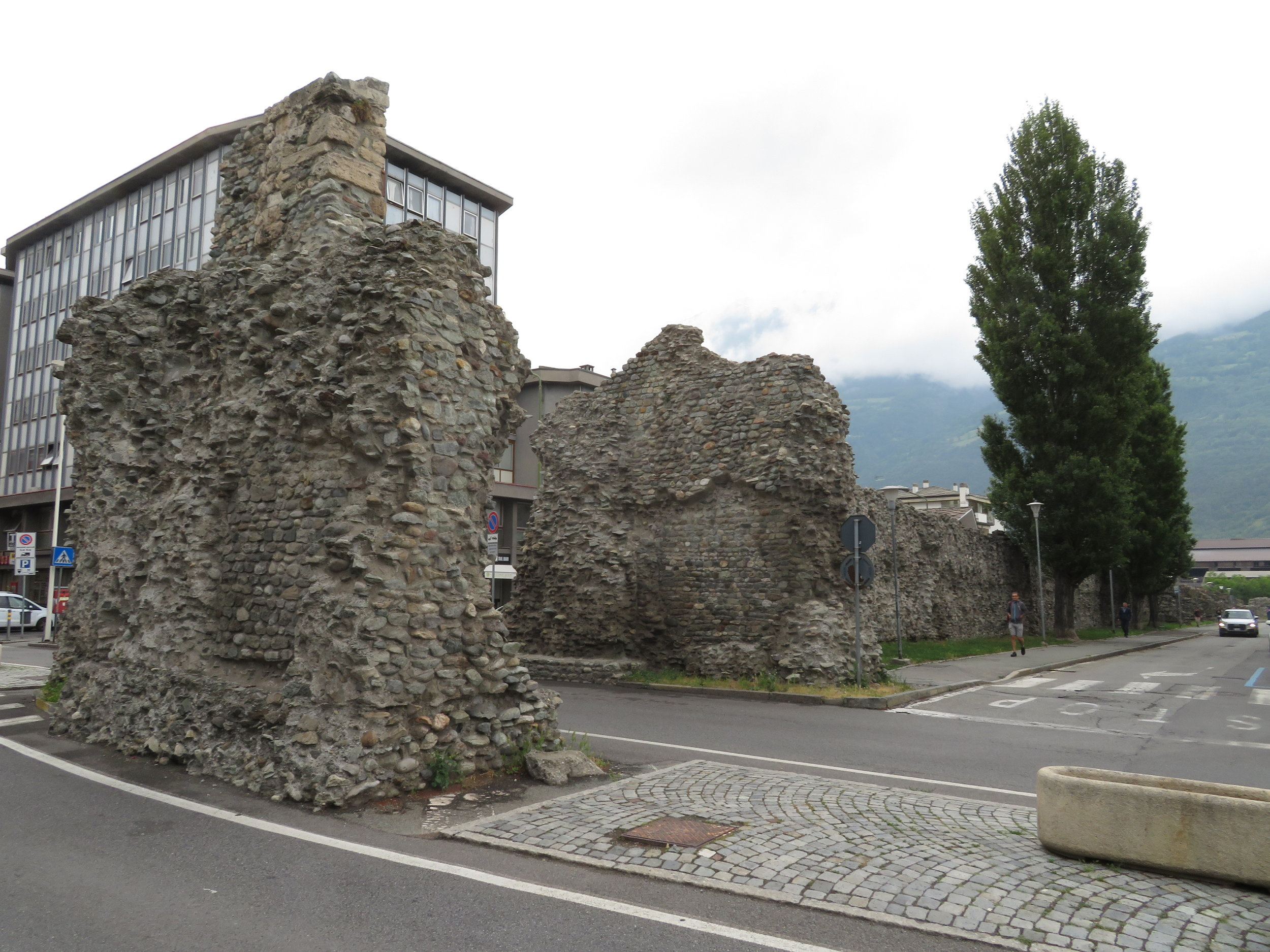 Ruins of a Roman wall right in the middle of town. Traffic diverts around it or passes through the middle.