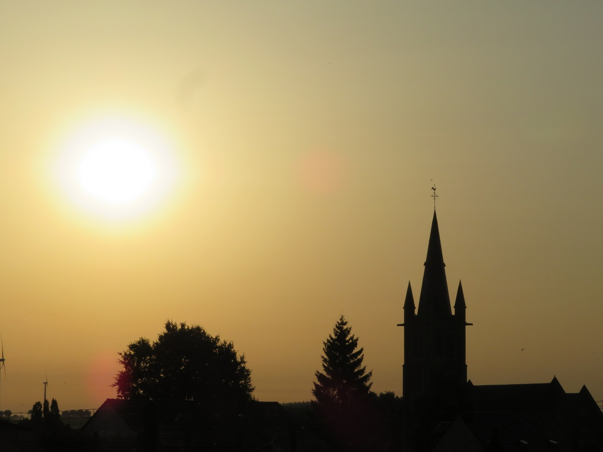 Village church steeple silhouetted in the blazing sun.