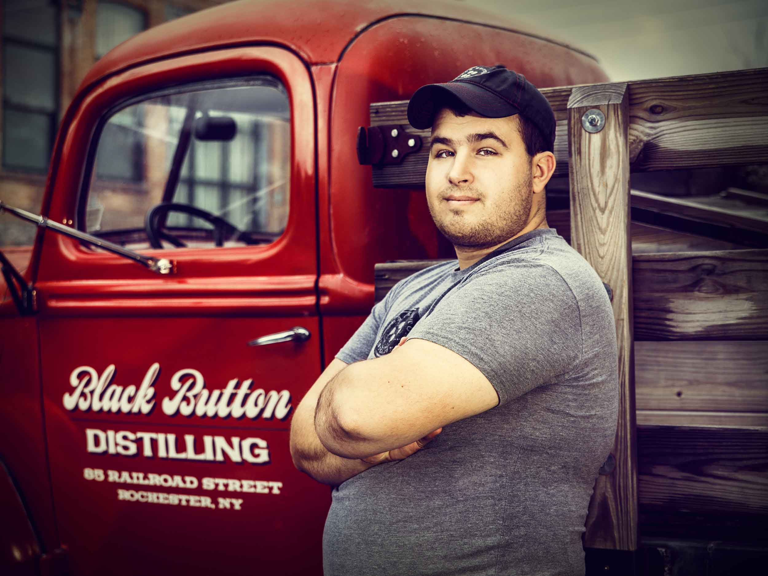 Owner and creator of Black Button Distilling, Jason Barrett, stands harms folded and smiling in front of Black Button Distilling Farm Truck