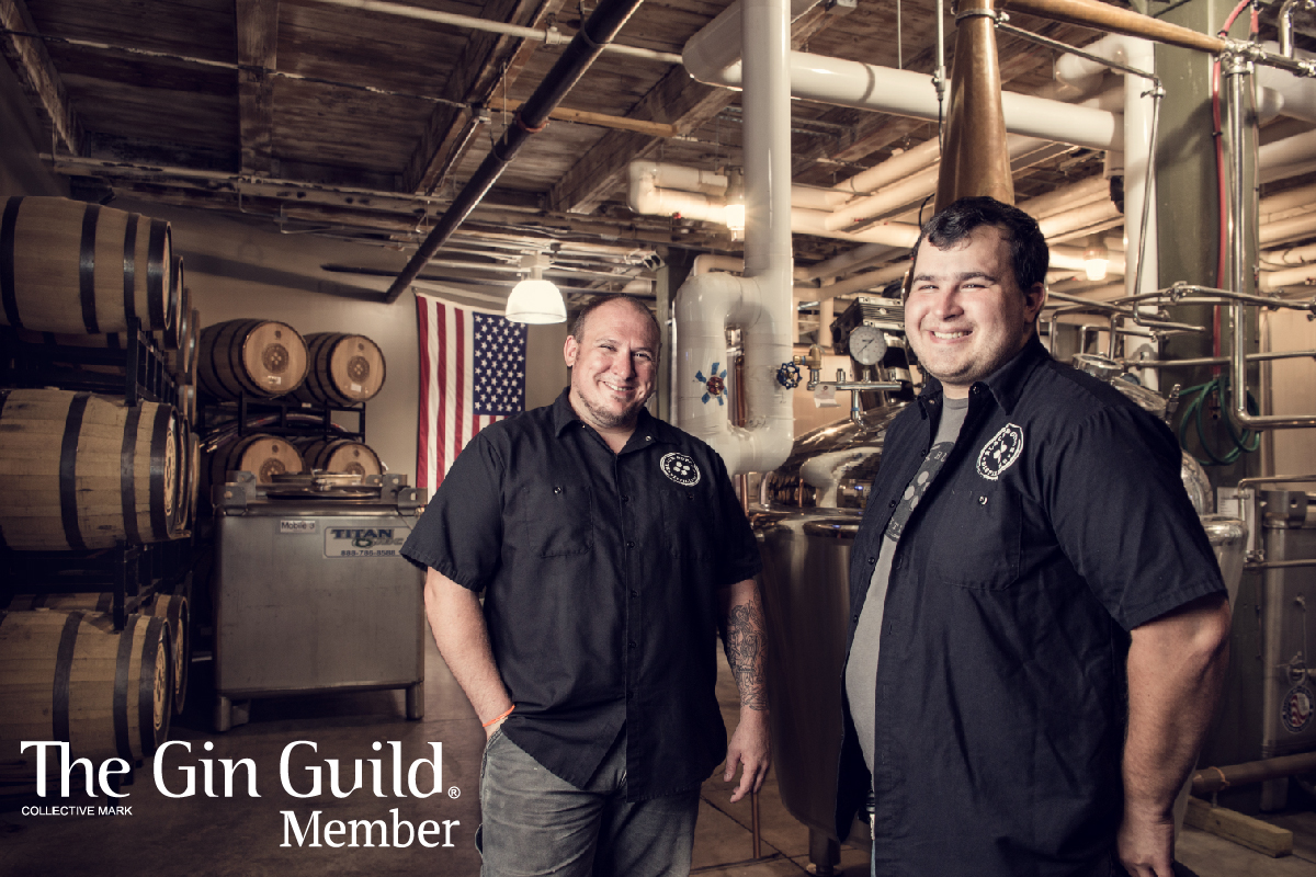Jason Barrett and Jeff Fairbrother stand  side by side smiling in front of Black Button Distilling's production facility