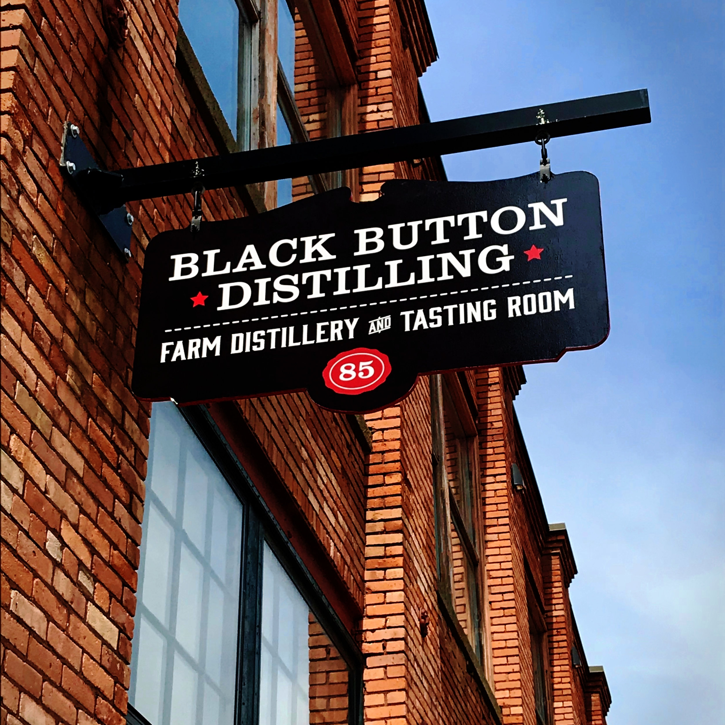 Black Button Distilling Farm Distillery and Tasting Room sign outside of Railroad Street