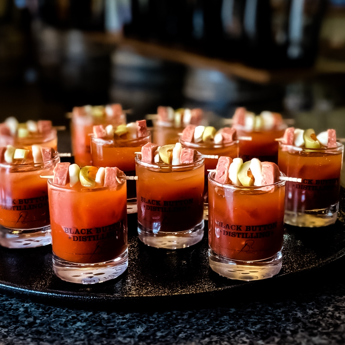 Several Small Bloody Mary cocktails on a tray