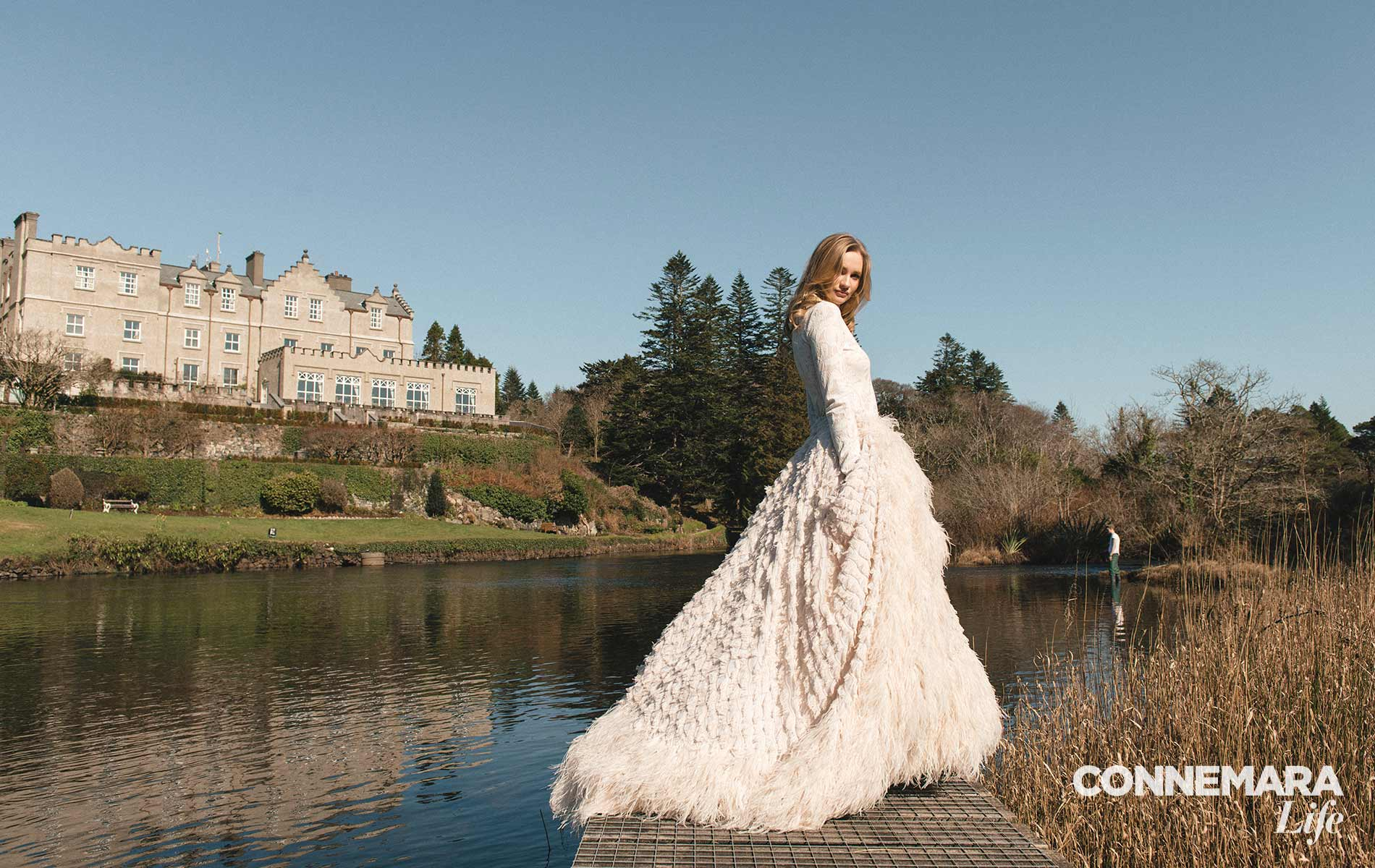 Model wearing Christian Siriano sheer long-sleeve knit top and ivory feathered fringe ball gown, location at Ballynahinch Castle, Galway.