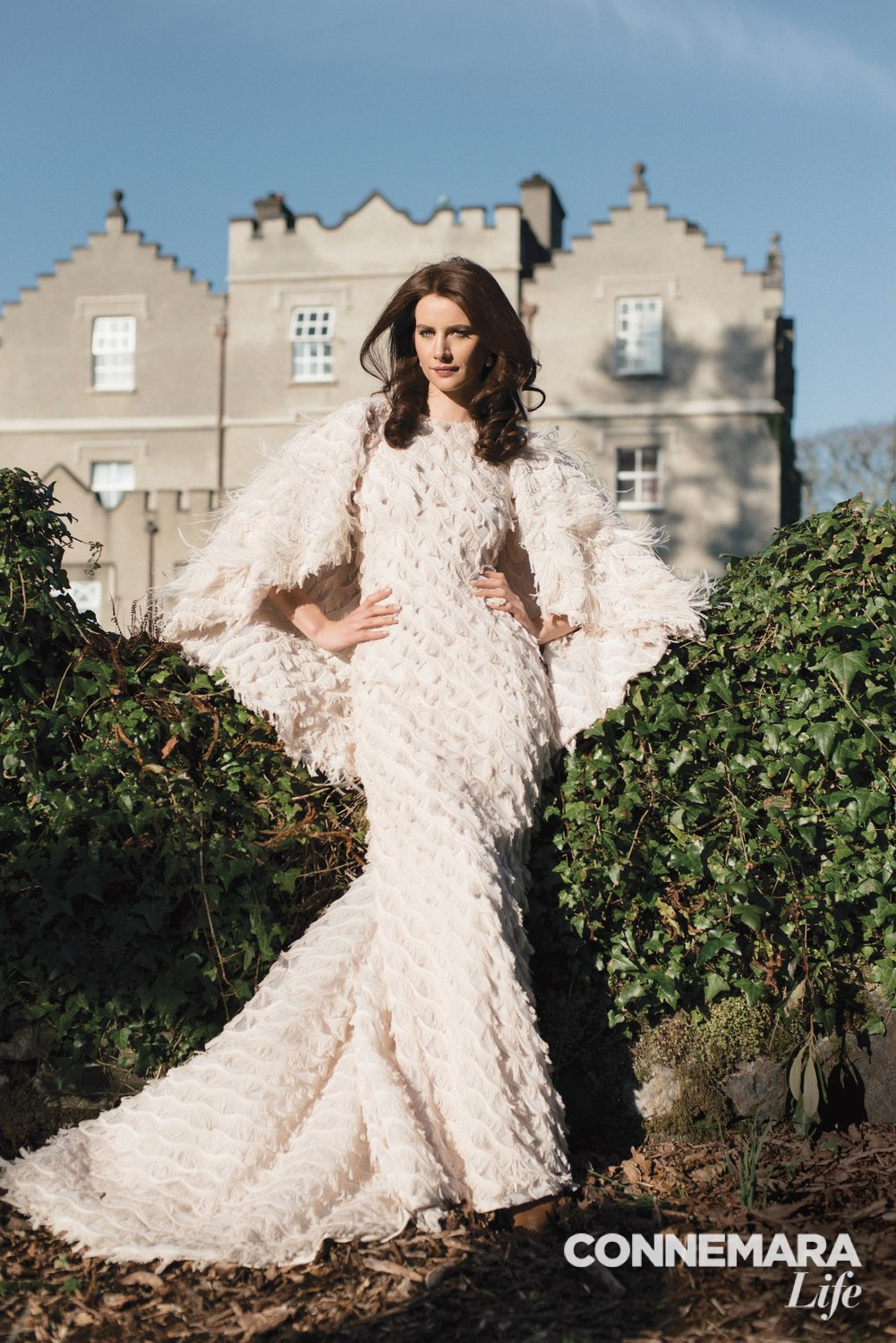 Christian Siriano ivory feathered fringe cape gown; 18ct yellow gold and baroque freshwater pearl earrings by Yvel