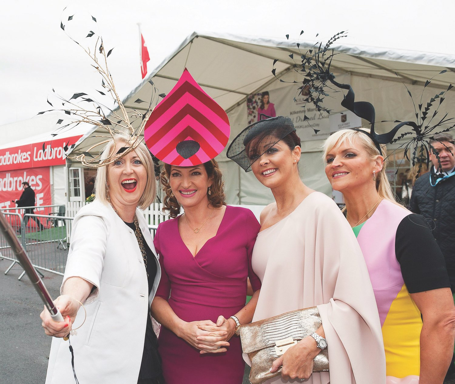 Attendees pose for a selfie adorning their couture hats.