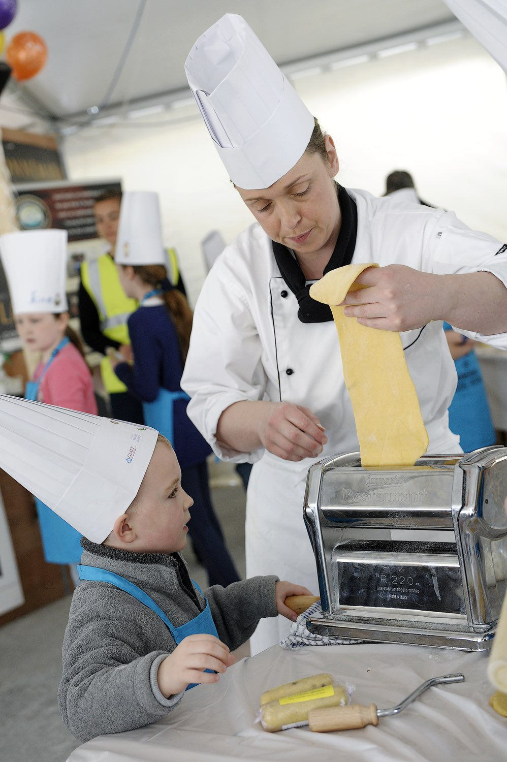 Chef showing child how to roll out dough