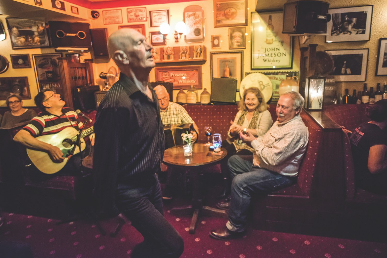 Onlookers watch man dancing to music in Irish Pub
