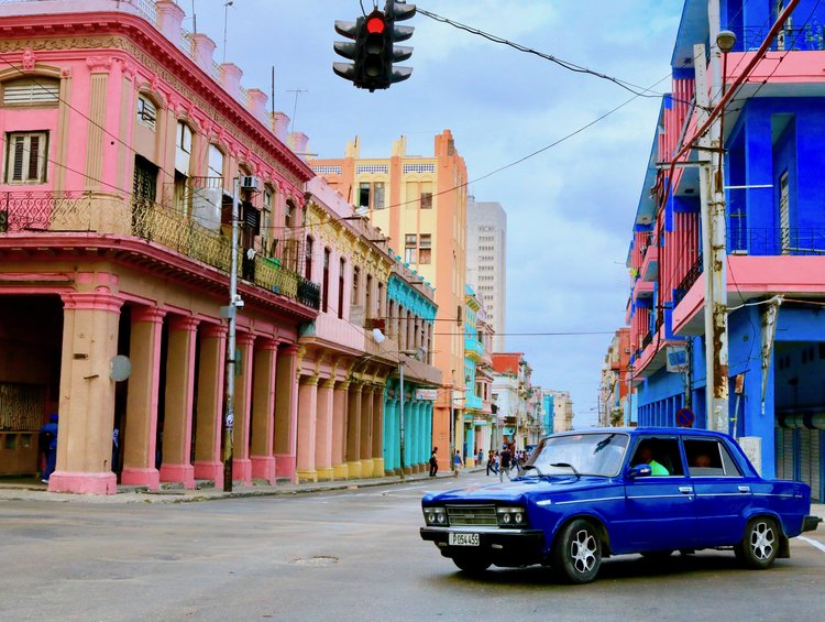 Photograph of Cuban city street with blue car and buildings by Fern Chavez